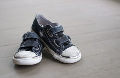 Little Boys Shoes. A still life background image of a small boy's shoes.  Wear and tear are purposefully included in detail.  There is plenty of copy space Stock Images