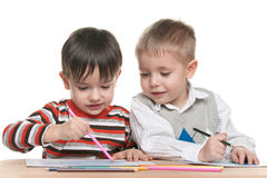 Little boys sit at the desk and write Stock Photography