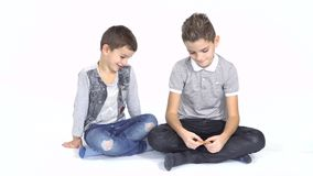 Little boy shares cookie with younger brother at white background stock video footage