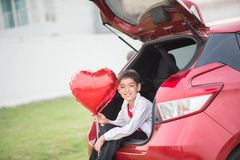 Little boys sitting on the back door of the car with balloon heart hand stock photo
