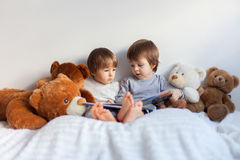 Little boys, sitting in bed, reading a book Royalty Free Stock Photography