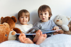 Little boys, sitting in bed, reading a book Royalty Free Stock Images