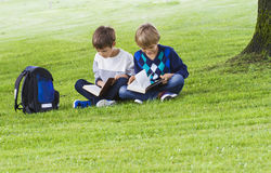 Little boys sitting on the grass in a park and reading books. School, education, people concept Royalty Free Stock Photography
