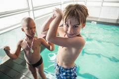 Little boys standing by the pool with medals. At the leisure center Royalty Free Stock Photo