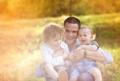 Little boys with their dad. Little boys and their dad enjoying their time together outside in nature royalty free stock photography