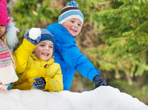 Little boys throw snowballs in the winter park Royalty Free Stock Images