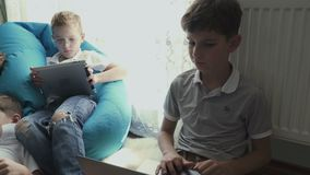 Little boys uses laptop and tablet at home. Little brothers spend their leisure time at home together. Children uses electronic gadgets at home. Children plays stock video