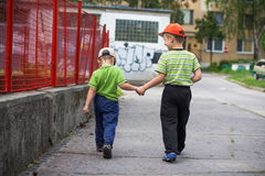 Little boys walking on sidewalk Stock Image