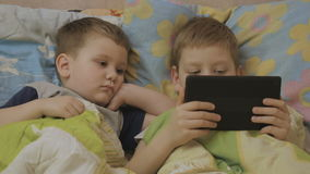 Little boys watching the cartoon. Kids want to sleep. children online before time to sleep stock footage