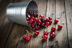 Little brass bucket of cherries on a table Stock Images