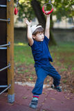 Little brave boy hanging on jungle gym Stock Photo