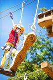 Little brave caucasian girl at outdoor treetop climbing adventure park. 7 years old girlie climbing in a rope playground structure in 5 meters high altitude royalty free stock photos