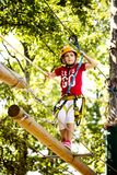 Little brave caucasian girl at outdoor treetop climbing adventure park. 7 years old girlie climbing in a rope playground structure in 5 meters high altitude royalty free stock images