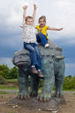 Little brave children on a dinosaur in a park royalty free stock photography