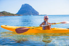 Little brave cute girl kayaking in the clear blue Royalty Free Stock Image