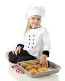 Little Bread-Baker. An adorable preschool chef sitting on the floor displaying fresh loaves of bread and buns in a pan.  On a white background Royalty Free Stock Photography