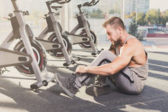 Handsome young man lace shoes at gym after training Royalty Free Stock Photography