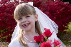 Little Bride 1. Portrait of an adorable little girl posing as a bride holding a bouquet of roses Stock Photography