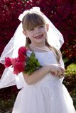 Little Bride 1. Portrait of an adorable little girl posing as a bride holding a bouquet of roses stock photos
