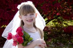 Little Bride 1. Portrait of an adorable little girl posing as a bride holding a bouquet of roses royalty free stock images