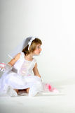 Little bride with cake in hand. Toddler girldressed up like a bride in a white gown with a piece of fake cake in her hand royalty free stock photo