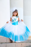 Little bride. A girl in a lush white and blue wedding dress Stock Image