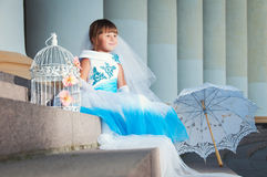 Little bride. A girl in a lush white and blue wedding dress and Royalty Free Stock Photo