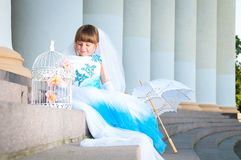 Little bride. A girl in a lush white and blue wedding dress Stock Photos