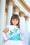 Little bride. A girl in a lush white and blue wedding dress. Stock Photos