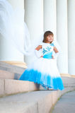 Little bride. A girl in a lush white and blue wedding dress and Stock Photos