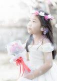 Little bride holding the rose bouquet, vintage tone Stock Image