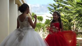 Little bride and little bride`s maids stay and play at churchyard while wedding ceremony is going on.