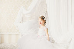 Little bride sitting on the bed Stock Photo