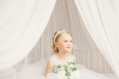 Little bride sitting on the bed. With bouquet Royalty Free Stock Image