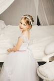 Little bride standing back at the bed Royalty Free Stock Images