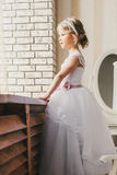 Little bride standing at window Stock Photos