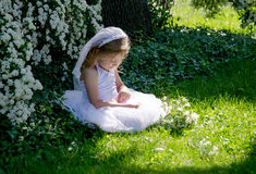 Little bride in a sunlit garden Stock Images