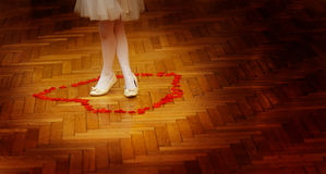 Little bridesmaid girl legs in white dress on wedding dancefloor with rose petals. Stock Photos