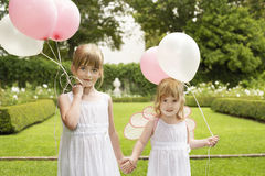 Little Bridesmaids Holding Balloons In Garden Stock Photo