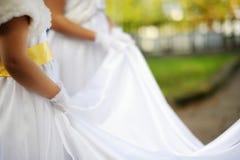 Little bridesmaids holding bride's dress Stock Photography