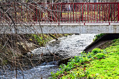 Little bridge in the city of winter Park. Fast flowing cold water and the trees are without leaves Royalty Free Stock Image