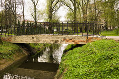 Little bridge over the creek in the park. A small bridge over the creek of the Pregol River in the city park of Kaliningrad Stock Photography