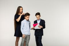 Little brother explains the task, older sister and brother want help him royalty free stock image