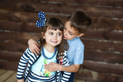 Little brother hugging little sister. A wooden background Stock Image