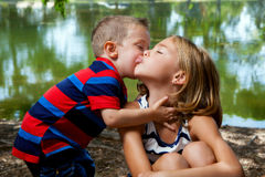 Little Brother Kisses Big Sister's Cheek. A little brother leans in to kiss his big sister on the cheek as she puckers her lips to the side of his face Stock Photos