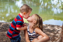 Little Brother Kisses Sister On Lips. A little brother leans in to give his a big sister a kiss on the lips Stock Photo