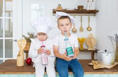 Little brother and little sister in cook cap drinking fresh juice with straw stock images