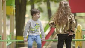 Little brother and older sister playing and talking on the playground. Siblings relationship. The girl arguing with the. Boy. Carefree childhood concept. Two stock video footage