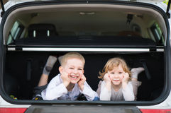 Little brother and sister in car boot Stock Photo