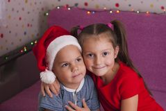 Little brother and sister. Charming girl hugging her little brother in a santa hat Stock Images